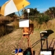 Plein air setup - easel, umbrella, painting, canvas, bags