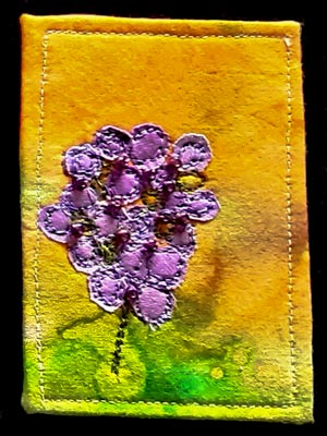 Artist trading card featuring a mauve flower on yellow green dyed background