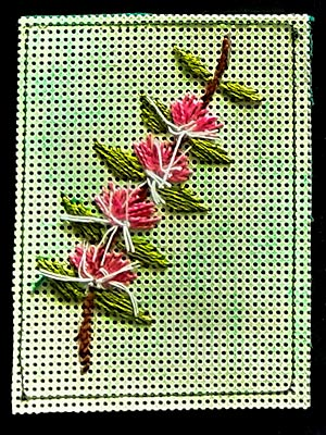 Artist trading card featuring embroidered flower spray on a green mesh background