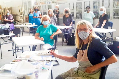 Group of artists wearing mask at work in the Peninsula Arts studio.