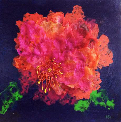 Flower made from textiles in warm red, orange and pink colours.