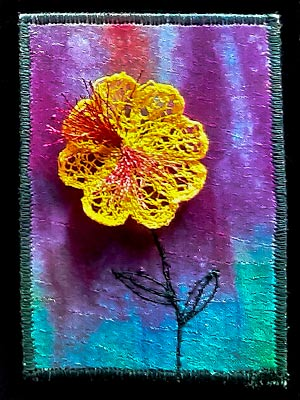 Artist trading card with a yellow flower on a multicoloured background in blues, greens and purples