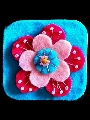 Multilayered fabric flower in pinks and blues on a blue background